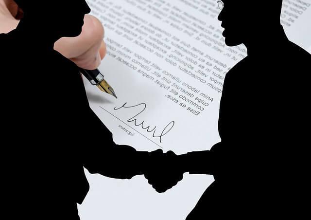 Договор аренды квартиры между юридическими. Рукопожатие двух бизнесменов на фоне подписанного договора