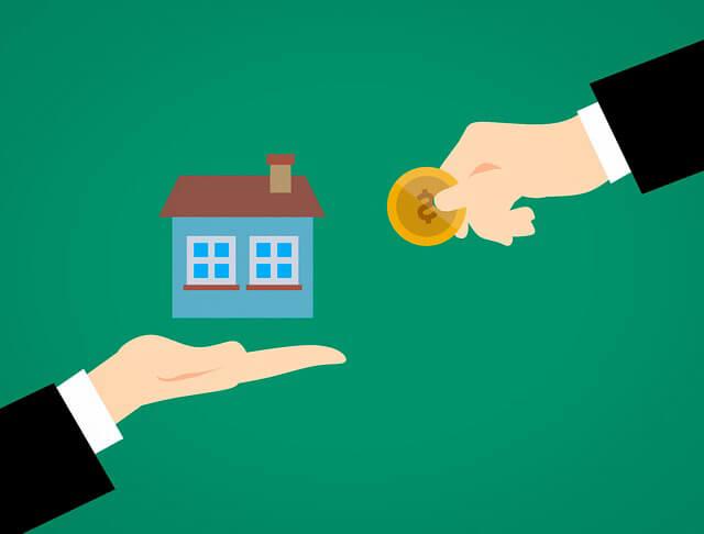 кто платит комиссию при аренде квартиры и сколько. Рука с деньгами на фоне дома