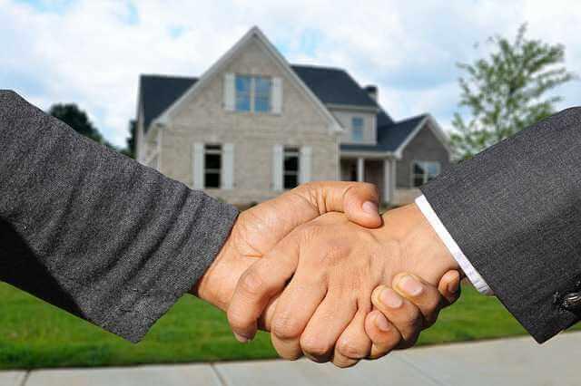 акт приема-передачи при сдаче квартиры в аренду, рукопожатие на фоне дома