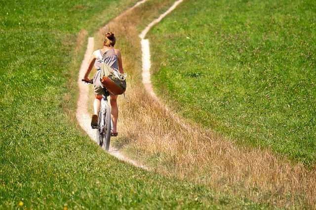как продать квартиру в другом городе, девушка едет на велосипеде в даль по полю