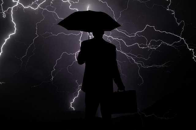стоит ли продавать квартиру в кризис, мужик под зонтом в грозу