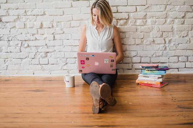 соглашение о содержании и выплате алиментов на ребенка, девушка сидит с ноутбуком на полу и что то заполняет