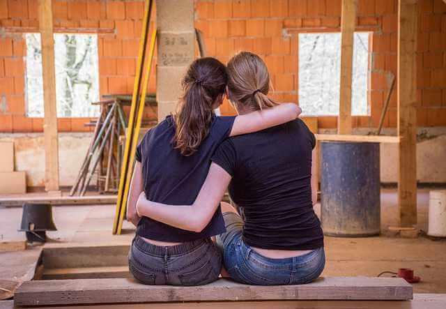 Что входит в капитальный ремонт многоквартирного дома, подруги сидят обнявшись и смотрят на ремонт в квартире