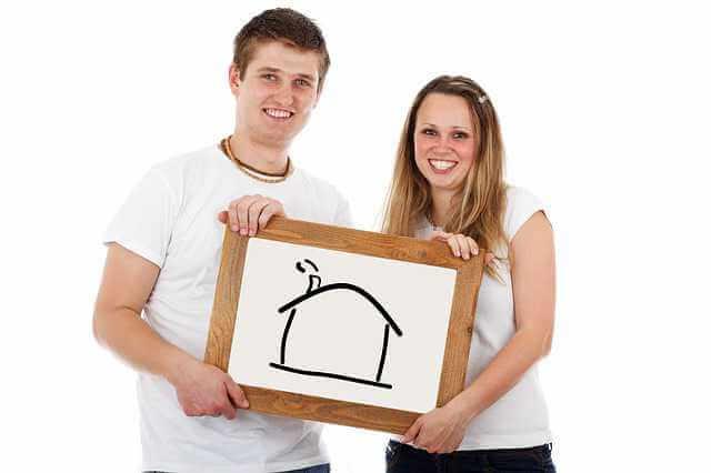 Плюсы и минусы ипотеки,молодая пара держит в руках картину с домом