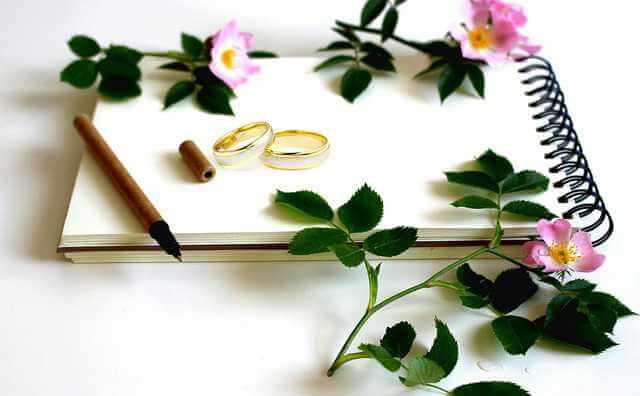 восстановить свидетельство о заключении брака, обручальные кольца лежат на блокноте с карандашем