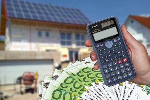 Какая должна быть зарплата для ипотеки,рука с калькулятором на заднем фоне идет строительство дома