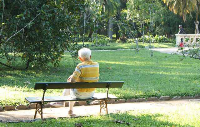 Обратная ипотека,пожилой человек сидит на лавочке спиной