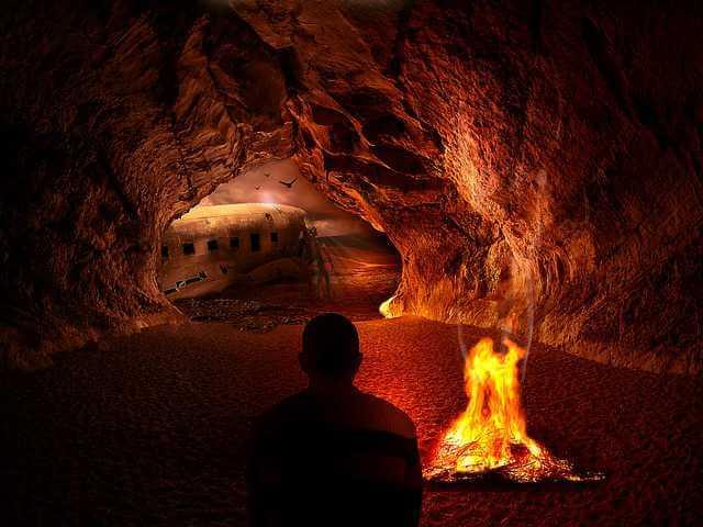Причины отказа в ипотеке, человек сидит в пещере с костром