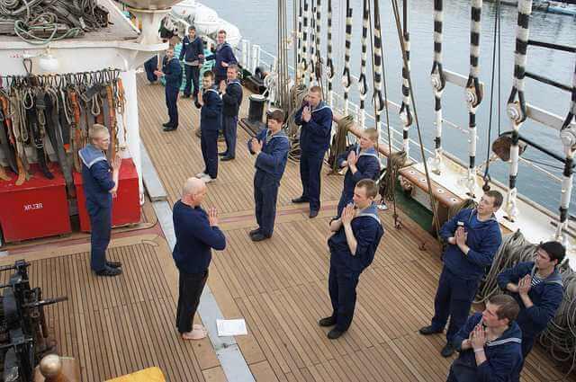 Ипотека для моряков в Сбербанке, моряки на палубе занимаются йогой скрестив руки на груди