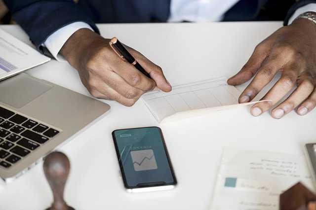 Как Сбербанк проверяет заемщиков, человек пишет на бумаге лежит телефон на столе и ноутбук