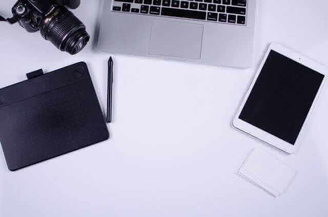 Договор купли-продажи квартиры по ипотеке Сбербанка, ноутбук лежит на столе, а редом с ним лежат ручка,фотоаппарат,планшет...