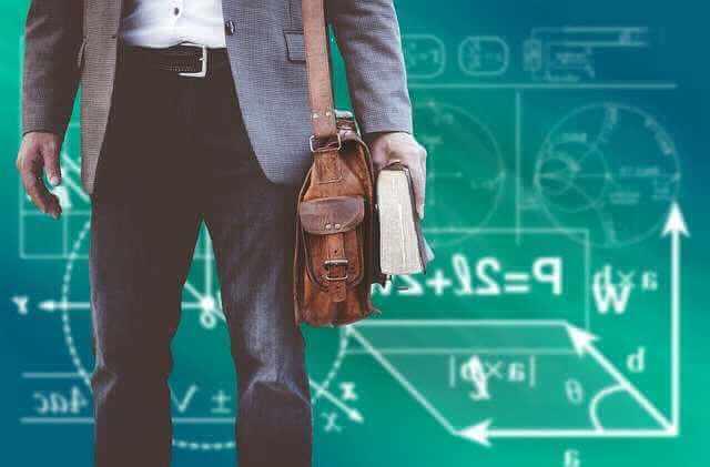 ипотека для учителей в Сбербанке, учитель возле доски с книгой в руках и с портфелем