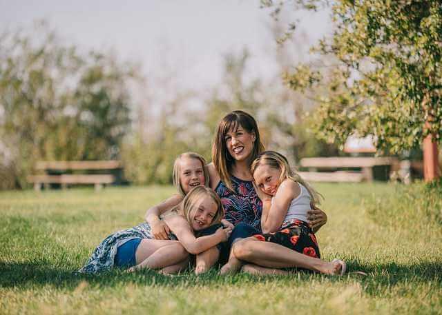 Ипотека многодетным семьям в Сбербанке, мама сидит с тремя детьми на полянке и обнимает их