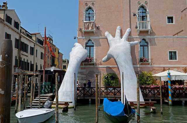 Коммерческая ипотека для физических лиц, руки из бетона охватывают угол дома, скульптура в Венеции
