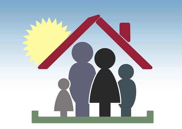 Оценка недвижимости для ипотеки в Сбербанке, семья стоит под крышей своего дома, на улице солнце.