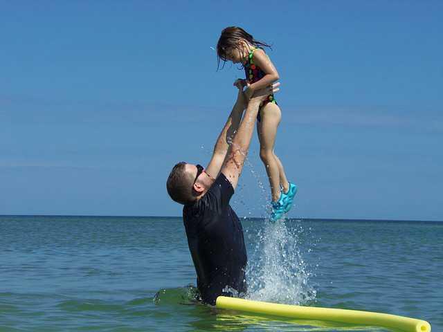 Снижение  ипотеки в Сбербанке при рождении ребенка, отец радостно поднимает девочку на руках вверх