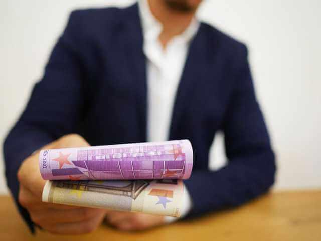 Досрочное погашение ипотеки в Сбербанке, человек сидит за столом и протягивает деньги