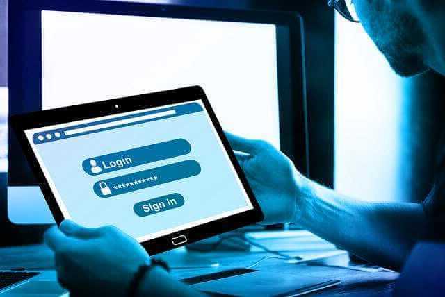 Электронная регистрация сделки с недвижимостью через Сбербанк, человек с планшетом возле компьютера проходит регистрацию