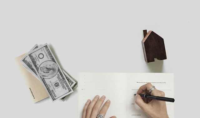 ипотека по двум документам в Сбербанке, пачка денег домик и рука которая подписывает документ