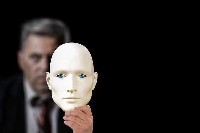 Ипотека самозанятым в Сбербанке, человек держит на вытянутой руке маску, которая частично закрывает его лицо.