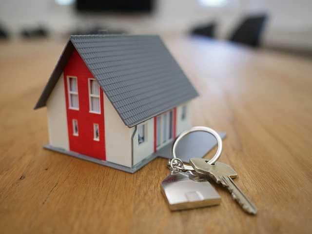Продать ипотечную квартиру Сбербанка,домик стоит на столе и рядом лупа и ключи