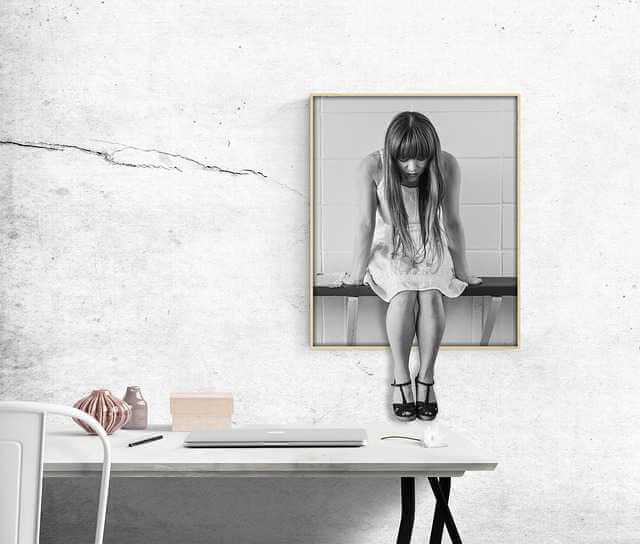 просрочка по ипотеке в Сбербанке, девушка сиди с опущенной головой