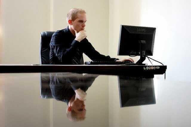 как узнать свой страховой стаж, мужчина сидит за столом и смотрит в монитор компьютера