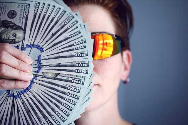 работодатель задерживает зарплату, девушка в очках закрывает лицо веером из денег
