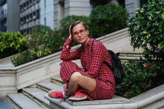 Ипотечные каникулы в банке ВТБ, девушка с рюкзаком сиди на ступеньках
