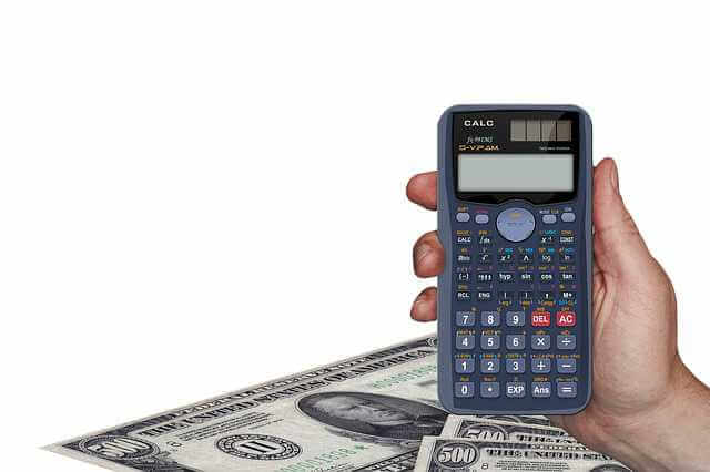 Расчет при увольнении по собственному желанию, калькулятор в руке на фоне денег