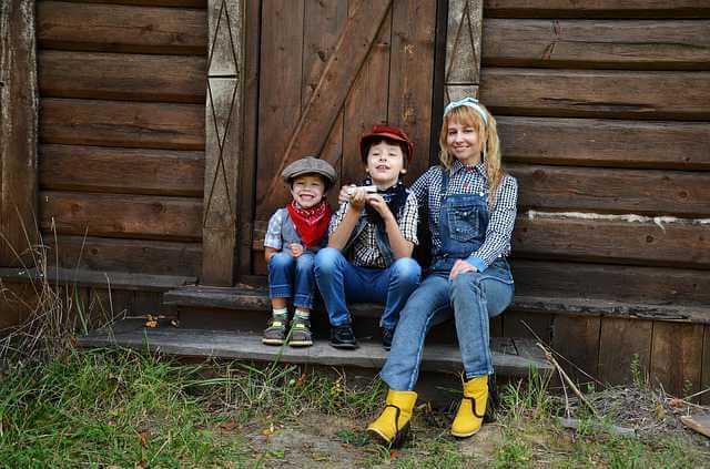 Сельская ипотека в Россельхозбанке, мама с детьми сидит на крыльце старого дома в селе