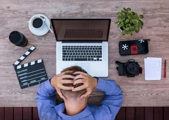 работодатель вынуждает уволиться, человек перед компьютером сидит и держится за голову