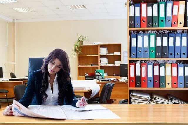 Причины увольнения по ТК РФ, девушка сидит и читает материалы