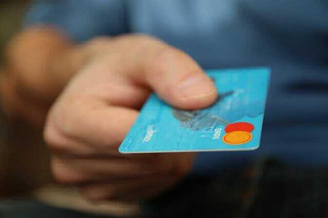 Ипотека в Газпромбанке для держателей зарплатных карт, человек протягивает банковскую карту газпромбанка