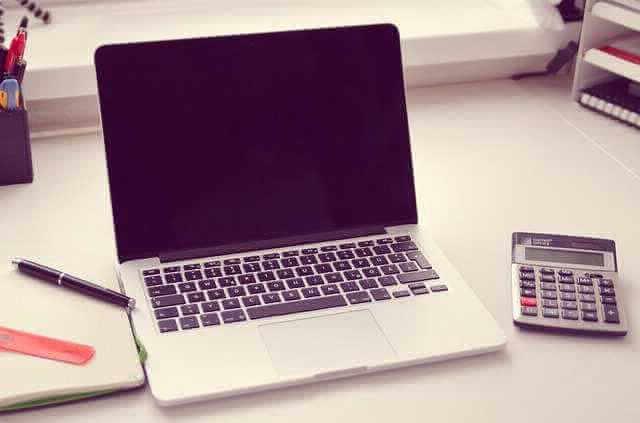 Калькулятор ипотеки от Газпромбанка, ноут стоит на столе и калькулятор