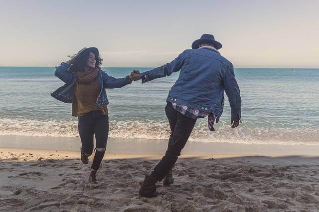 Досрочное погашение ипотеки материнским капиталом,молодая парочка кружиться держав друг друга за руки на фоне моря
