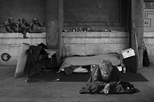 Намеренное ухудшение жилищных условий, мужик сидит на полу в полном беспорядке