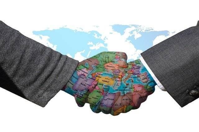 как заключить договор с иностранной компанией, рукопожатие на фоне карты мира